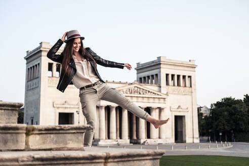 Happpy young woman dancing on stairs at Koenigsplatz, Munich, Germany - WFF00170