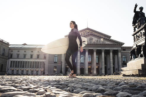 Young woman with surfboard on the way to Eisbach, Munich, Germany - WFF00194
