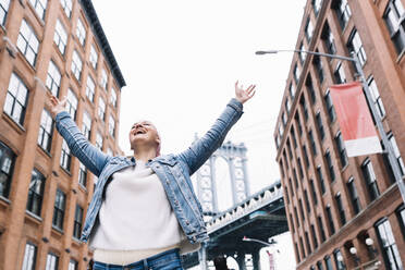 Woman with cancer bandana and raised arms at Manhattan Bridge in New York, USA - DAMF00225