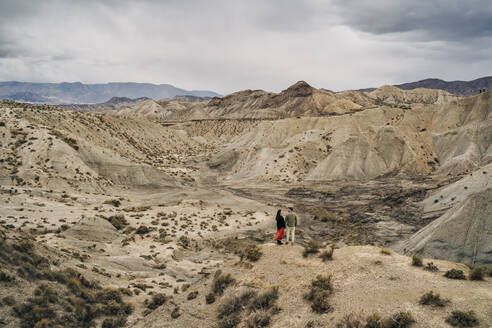 Young couple in desert landscape under cloudy sky, Almeria, Andalusia, Spain - MPPF00246