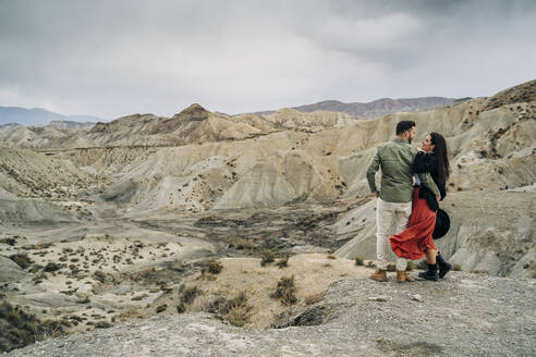 Young couple in desert landscape under cloudy sky, Almeria, Andalusia, Spain - MPPF00249