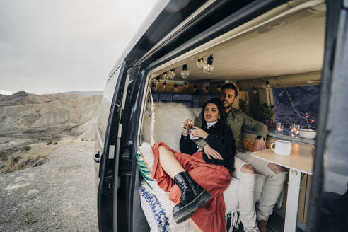 Young couple inside camper van in desert landscape, Almeria, Andalusia, Spain - MPPF00252