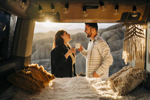 Young couple on a trip with camper van at sunset, Almeria, Andalusia, Spain - MPPF00264