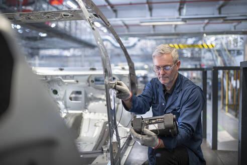 Engineer testing car body in car factory - CUF53303