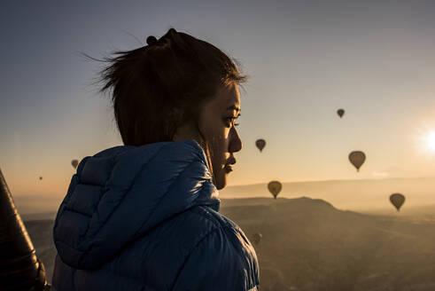 Woman enjoying view, hot air balloons flying in background, Göreme, Cappadocia, Nevsehir, Turkey - CUF53489