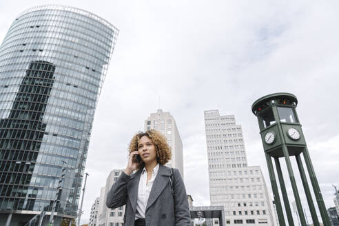 Woman on the phone with office buildings in background, Berlin, Germany - AHSF01262