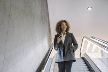 Woman holding cell phone on escalator - AHSF01268