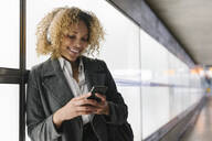 Smiling woman with headphones and smartphone - AHSF01274