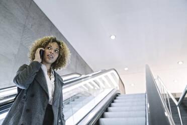 Woman on the phone on escalator - AHSF01286