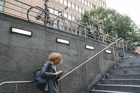 Woman using smartphone at the entrance of a subway station, Berlin, Germany - AHSF01289
