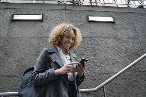 Smiling woman using smartphone at the entrance of a subway station, Berlin, Germany - AHSF01292
