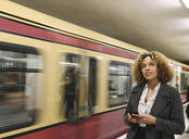 Woman with cell phone in subway station as the train comes in - AHSF01295
