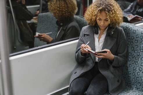 Woman taking notes on a subway - AHSF01298