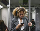 Woman using smartphone on a subway - AHSF01301