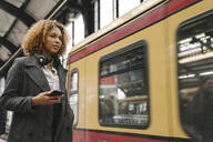 Woman with cell phone in subway station as the train comes in - AHSF01304