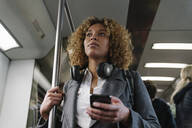 Woman with smartphone on a subway - AHSF01307