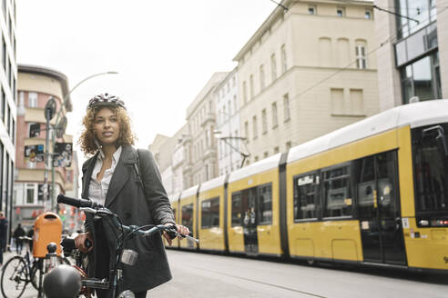 Woman with bicycle in the city, Berlin, Germany - AHSF01316