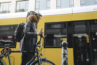 Woman commuting with a bicycle in the city, Berlin, Germany - AHSF01319