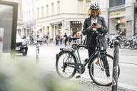 Woman with bicycle and smartphone in the city, Berlin, Germany - AHSF01322