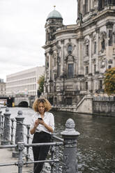Tourist woman using smartphone in the city at Spree river, Berlin, Germany - AHSF01331