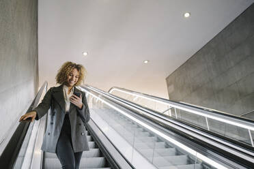 Smiling woman using cell phone on escalator - AHSF01334