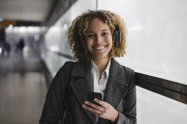 Portrait of smiling woman with headphones and smartphone - AHSF01340