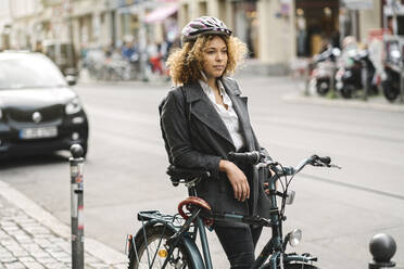Woman with bicycle in the city, Berlin, Germany - AHSF01346