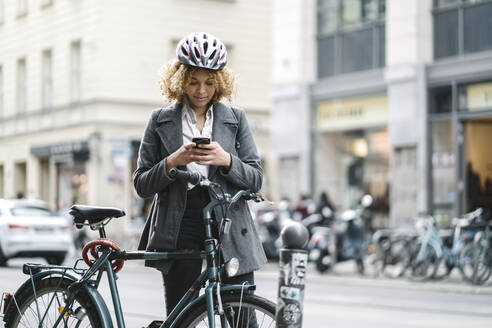 Woman with bicycle and smartphone in the city, Berlin, Germany - AHSF01349