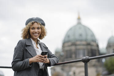 Portrait of happy tourist woman in the city with Berlin Cathedral in background, Berlin, Germany - AHSF01352