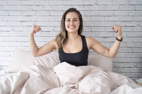 Portrait of happy young woman sitting on bed flexing muscles - FBAF00948