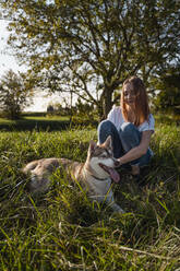 Happy young woman stroking her dog on a meadow - MAUF03078