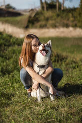Happy young woman hugging her dog on a meadow - MAUF03081