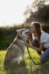 Young woman nose to nose with her dog on a meadow - MAUF03090