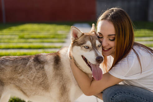 Happy young woman cuddling her dog - MAUF03096