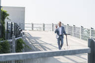 Happy mature businessman with e-scooter and smartphone on parking deck - UUF19698
