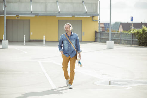 Casual mature man with headphones and skateboard walking on parking deck - UUF19710
