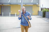 Casual mature man using smartphone walking on parking deck - UUF19713