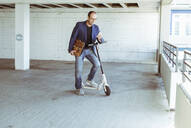 Mature businessman with e-scooter and smartphone in parking garage - UUF19716