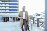 Mature businessman with smartphone and briefcase walking on parking deck - UUF19722