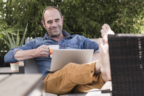Smiling mature man sitting on terrace with earphones and laptop - UUF19734
