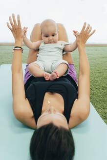 Young mother and baby exercising on yoga mat - MPPF00282
