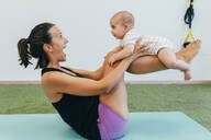 Young mother and baby exercising on yoga mat - MPPF00288