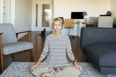 Mature woman practicing yoga at home - VABF02403