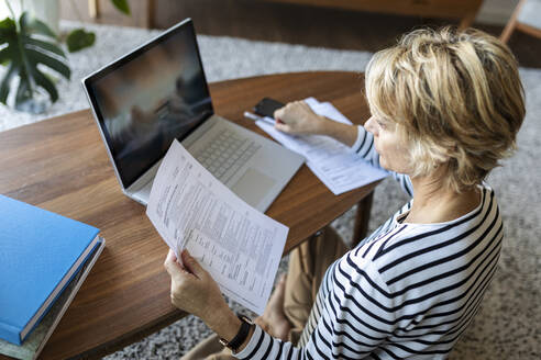 Mature woman with documents using laptop at home - VABF02415