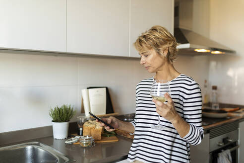 Mature woman drinking wine and using her smartphone in kitchen at home - VABF02436