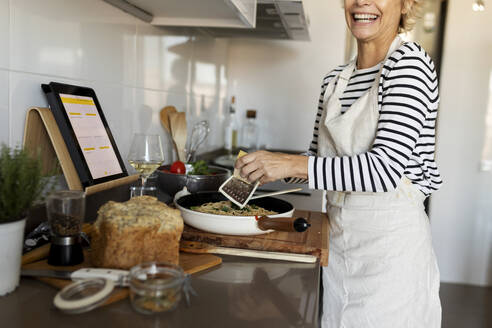 Happy mature woman with tablet cooking pasta dish in kitchen at home - VABF02448