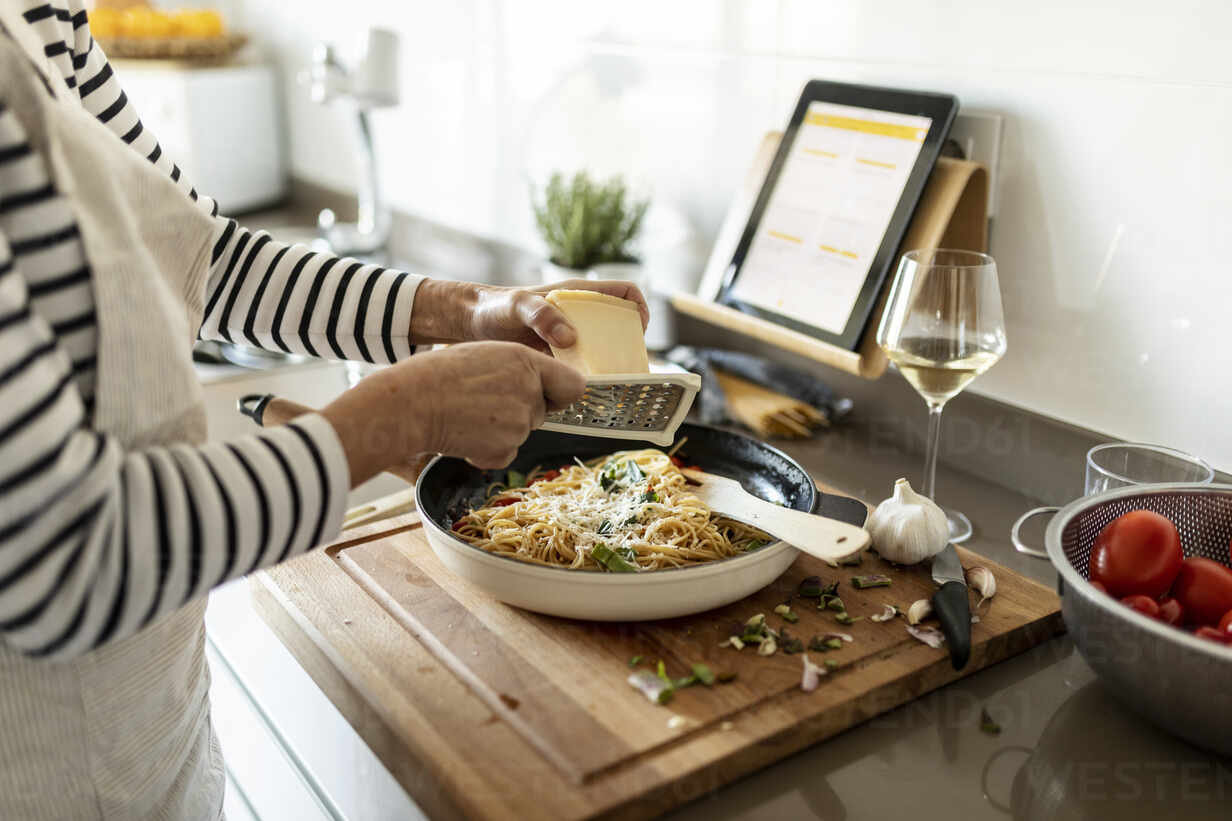 Close-up of woman with tablet cooking pasta dish in kitchen at home - VABF02451 - Valentina Barreto/Westend61