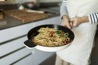 Close-up of woman holding a pan with pasta dish in kitchen at home - VABF02457