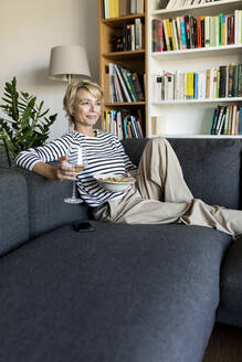 Mature woman eating homemade pasta dish and drinking wine on couch at home - VABF02460
