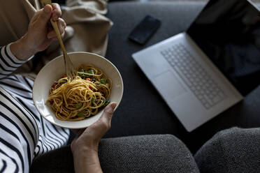 Mature woman with laptop eating homemade pasta dish on couch at home - VABF02463